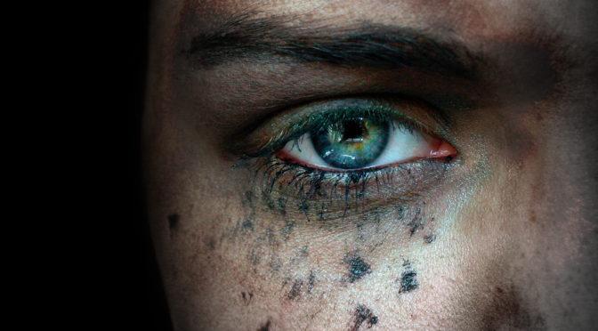 Sinnemanie Logo, Nahaufnahme eines Gesichts in einem schwarzen Raum, nur ein Auge und Nasenhälfte sind zu erkennen